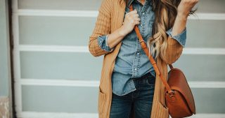 girl wearing denim top with denim jeans and long ribbed brown cardigan and crossbody brown bag long loosely curled hair with caramel ombre