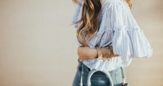 girl wearing flutter sleeve top with blue and white stripes with distressed jeans and wedges with crcossbody bag and long loosely curled brown hair with ombre caramel