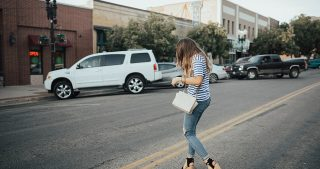 girl standing on road in distressed denim and stripe blue shirt with pink details black sam edelman wedges and crossbody bag
