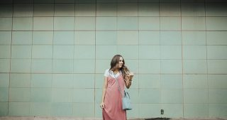 girl standing in pink slip dress with white tee shirt and light blue crossbody bag