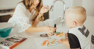 mom and little boy sitting at kitchen counter writing with paint sticks