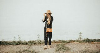 girl standing in black jumpsuit with brown hat and cognac crossbody bag