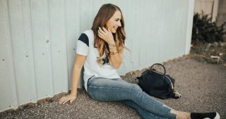 girl sitting on road in dallas cowboys apparel skinny jeans and black tassel flats with navy bag