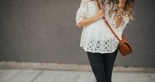 girl standing in lace top with dark denim jeans and crossbody sole society bag and black peep toe wedges