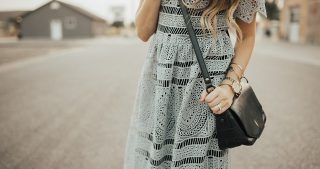 girl wearing grey lace dress with black crossbody bag and nude heels