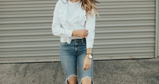 girl standing by wall with ruffle white top on with distressed denim jeans and loafters