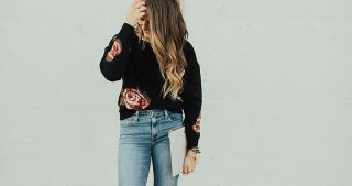 girl standing in black floral sweater with distressed jeans and brown booties
