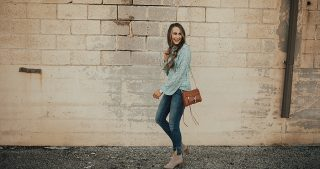 girl standing in green and white floral top with distressed denim brown booties and brown crossbody bag