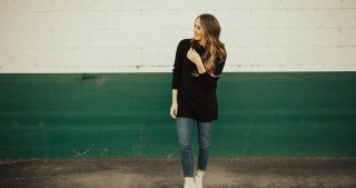 long tunic black sweater with distressed jeans and white booties