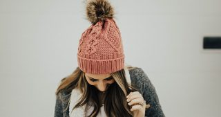 girl standing in pink beanie with pom pom on top with rose gold reebok sneakers jeans and sherpa cardigan