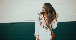 girl standing in white and pink bohemian maxi dress with booties and long loosely curled brown hair