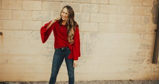 girl standing by brick wall with red bell sleeved sweater on with jeans and long loosely curled brown hair