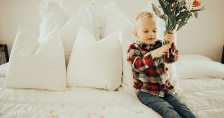 little boy sitting on bed with bouquet of flowers in red flannel shirt
